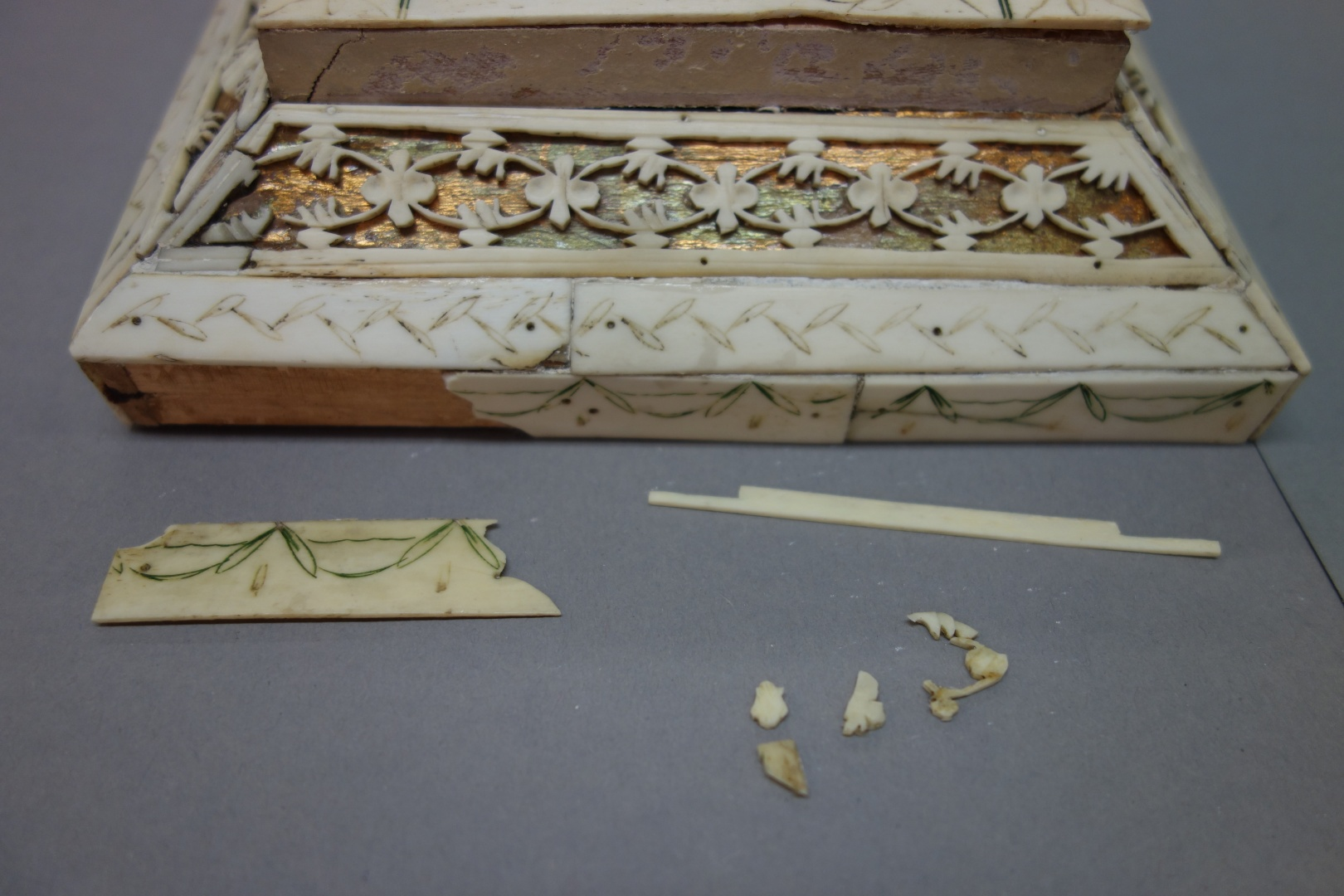 fig 9. Detached details and pieces of bone lace from the lid of the casket. Before fixing them, the casket was cleansed of loose dust. The surface cleansing was done with minimally dampened tampons