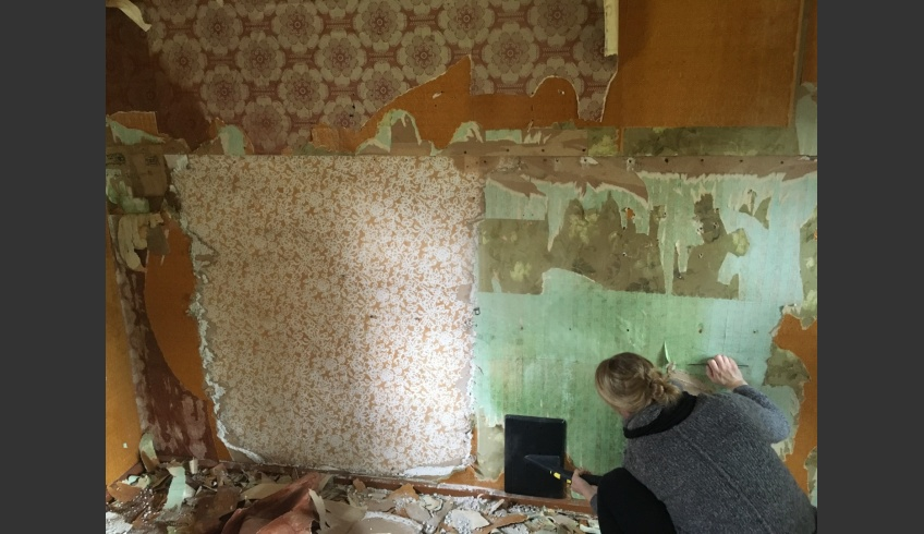 ill 12. Conservator Kristiina Ribelus opening wallpaper layers. On the left white-patterned wallpaper, the historically first layer that was underneath the plasterboard. Photo: Priit Rand