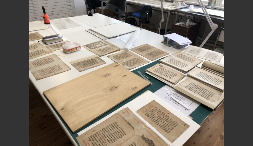 ill 24. Finishing touches on the folios, while arranging them into sections.