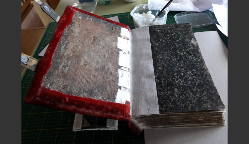 ill 47. The velvet fabric has been pasted onto the boards, the calico book binding cloth joint and filling cardboard follow will follow and lastly the marbled paper pastedown is fixed in place. © Tulvi Turo