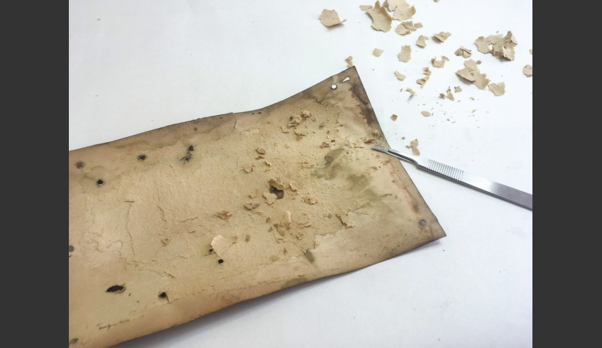 fig 9. It was decided to remove the deformed base cardboard that had moisture damage. The upper layers of the cardboard were removed dry with a scalpel. The residue and glue were detached with cotton wool dampened in the aqueous solution of methylated cellulose and distilled water